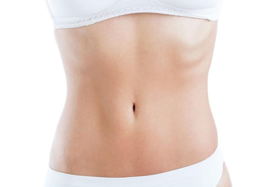 Close-up of slim woman body with flat abdomen